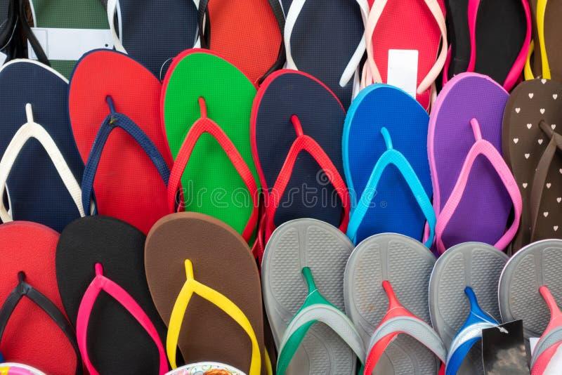 色的塑胶人字平底拖鞋 室外多彩多姿的鞋类为夏天 免版税库存照片