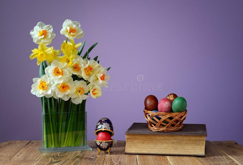 色的复活节彩蛋、书和花在花瓶 库存图片
