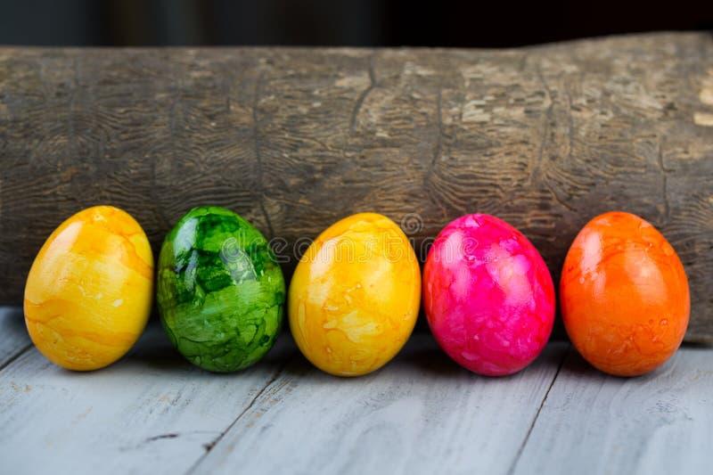 色的复活节彩蛋和木日志 免版税库存图片
