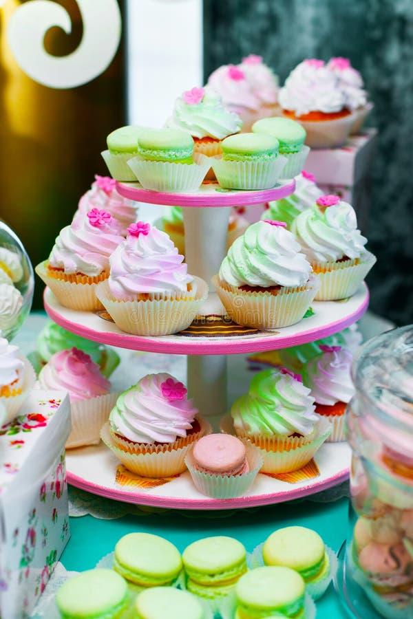 色的杯形蛋糕 与奶油的松饼 五颜六色的macarons 免版税库存图片