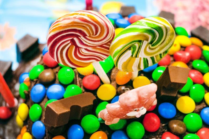 色的棒棒糖和巧克力糖衣杏仁在釉 免版税库存照片