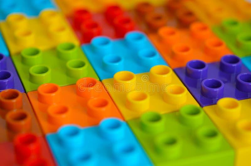 色的玩具砖 任意地计划了塑料积木,背景 儿童比赛 免版税库存图片
