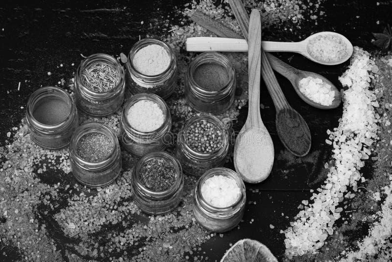 色的盐的构成和香料临近瓶子用草本 木匙子用辣椒粉、姜黄和海盐 图库摄影