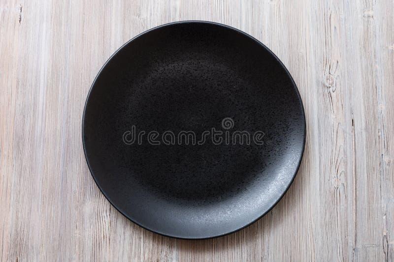 黑色的盘子顶视图在灰色棕色桌上的 免版税库存图片