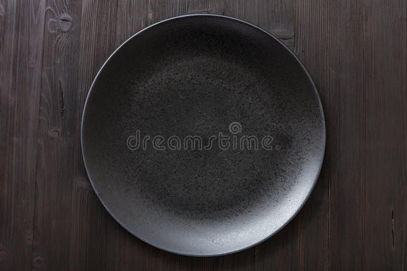 黑色的盘子顶视图在黑褐色桌上的 免版税图库摄影