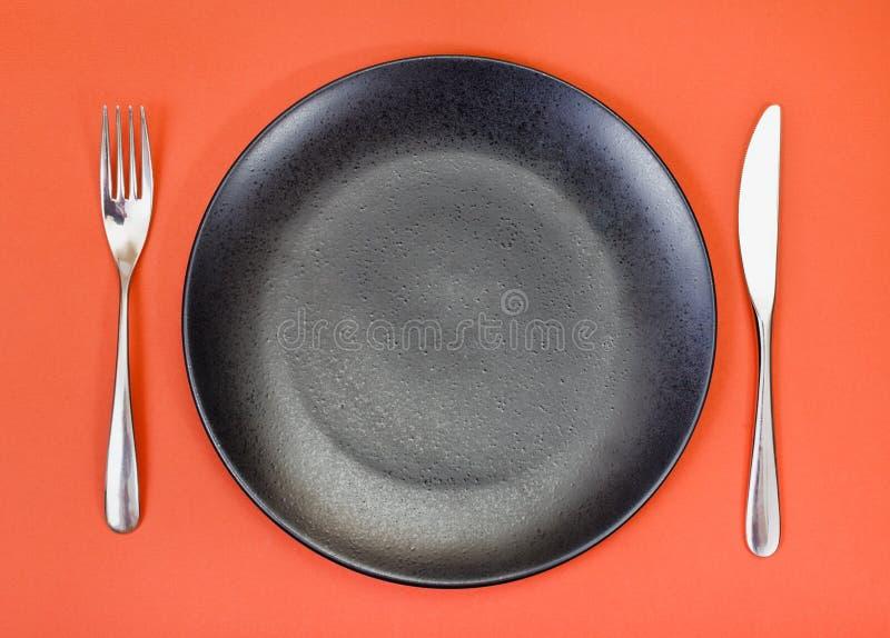 黑色的盘子,叉子,刀子顶视图在红色设置了 库存图片