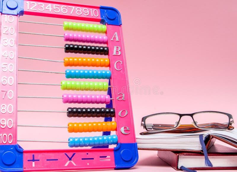 色的算盘、玻璃和笔记本在桃红色背景 教育,回到学校概念 库存照片