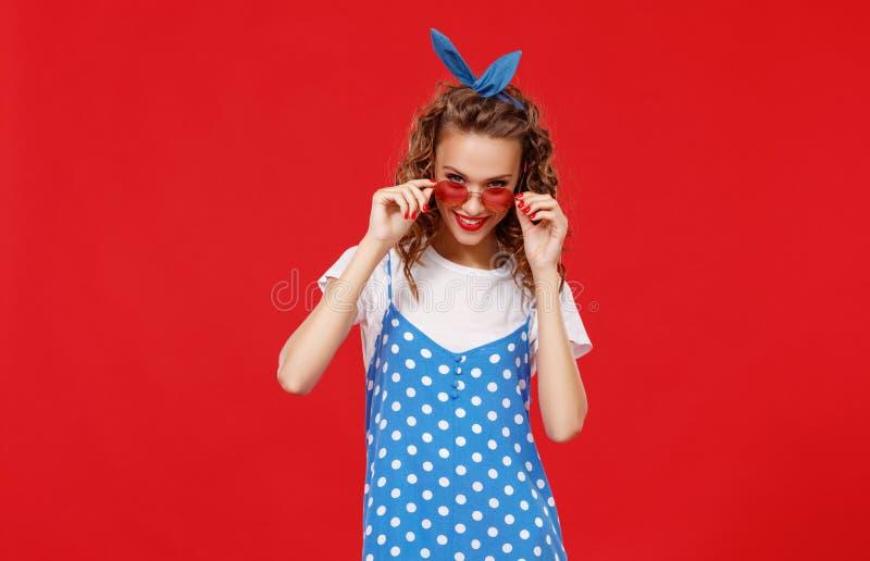 色的红色背景的美丽的滑稽的女孩 库存图片