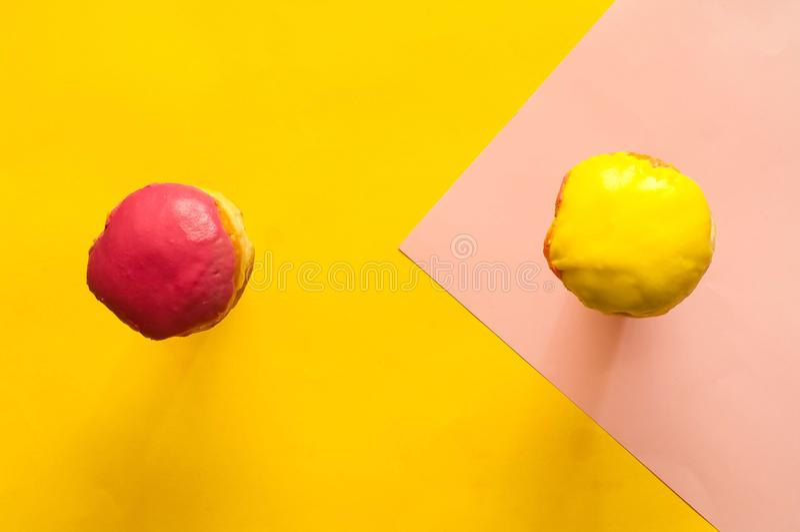色的给上釉的油炸圈饼在行动落或飞行反对桃红色和黄色淡色背景 宏观概念,特写镜头,拷贝空间 库存照片