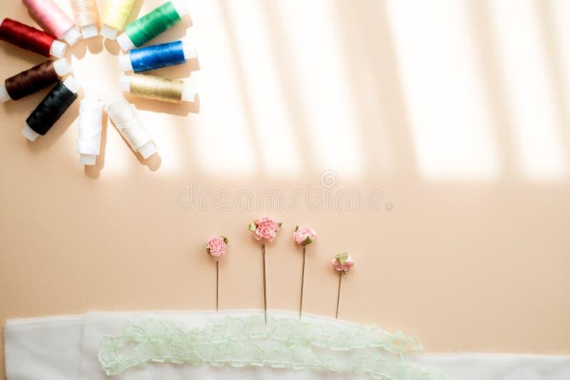 色的缝合针线和片盘在木背景 免版税库存照片