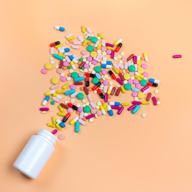 色的药片、片剂和白色瓶在orenge背景 免版税库存图片