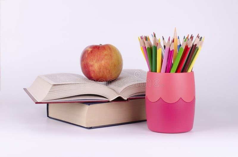 色的铅笔、书和苹果 免版税库存照片