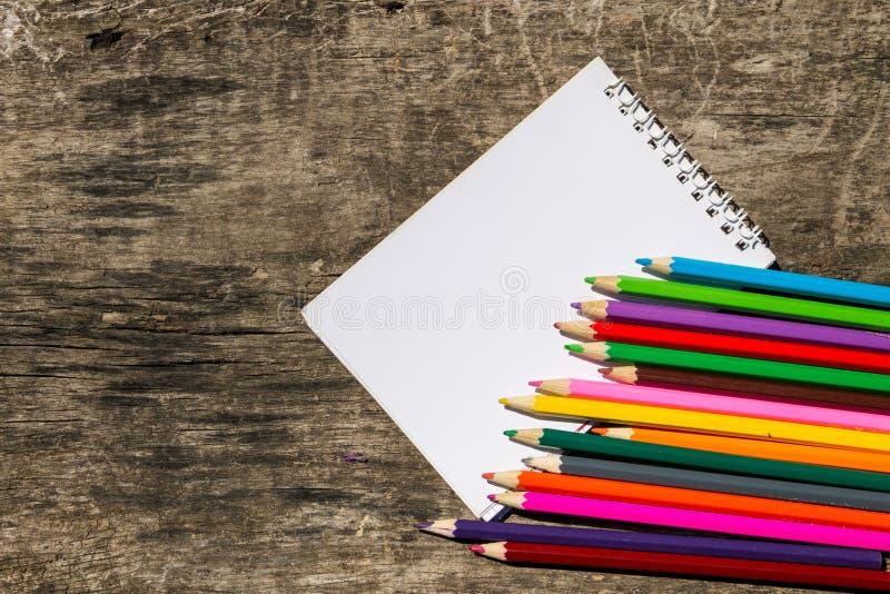 色的铅笔和空白的笔记薄在老木书桌上 免版税图库摄影