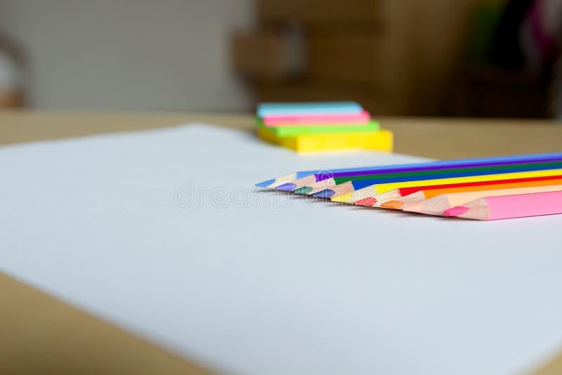 色的铅笔和贴纸在白色板料 免版税库存图片