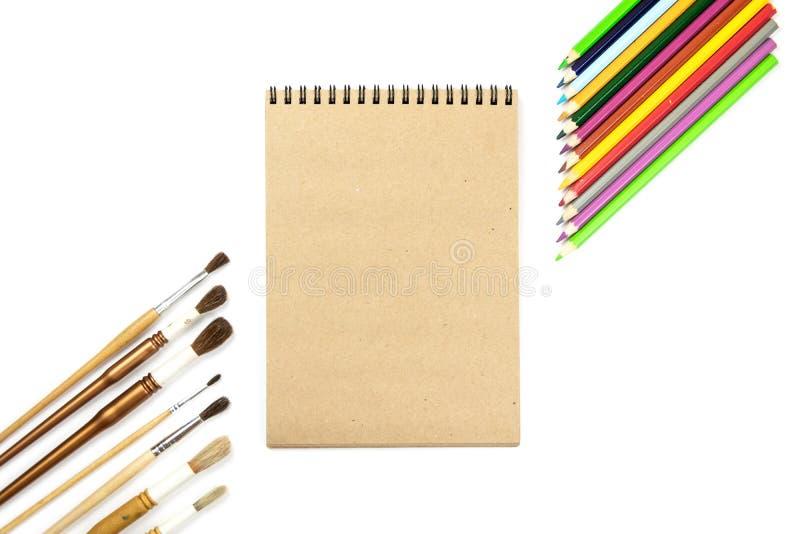 色的铅笔,刷子,笔记本嘲笑为与水彩油漆的艺术品 烙记的文具大模型场面, 免版税图库摄影