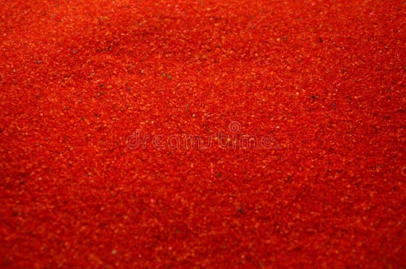 色的颗粒状沙子关闭的纹理  红色谷物 免版税库存照片