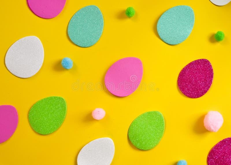 色的鸡蛋和小蓬松丛作为复活节的标志 鸡蛋由foamiran制成 图库摄影