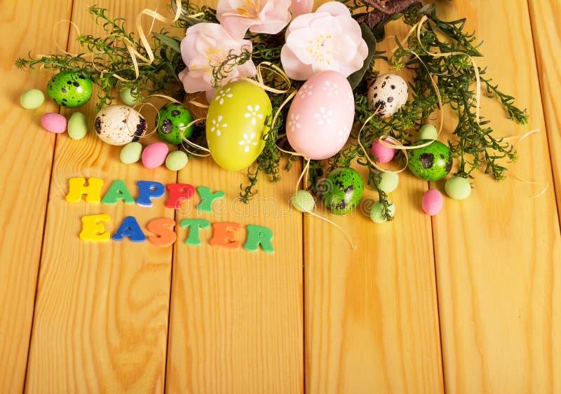 色的鸡蛋,花,糖果,措辞在轻的木头的复活节快乐 免版税库存图片