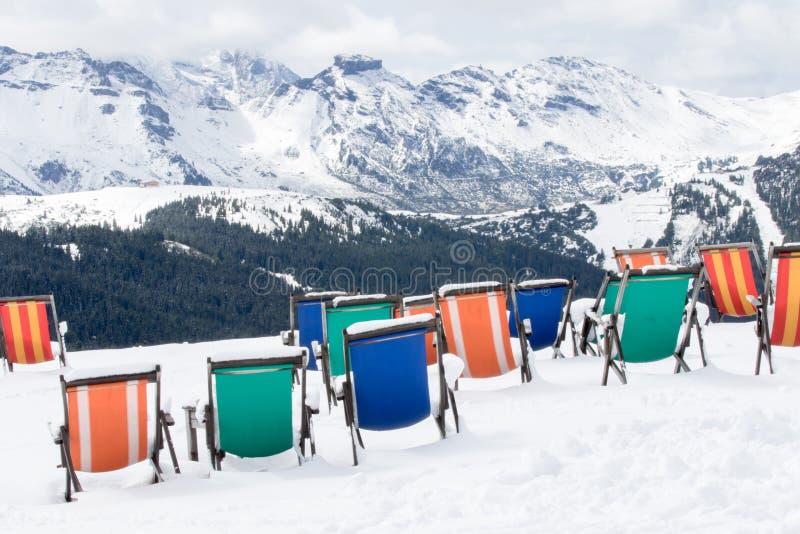 色的deckchairs系列在新鲜的雪被安装 库存照片
