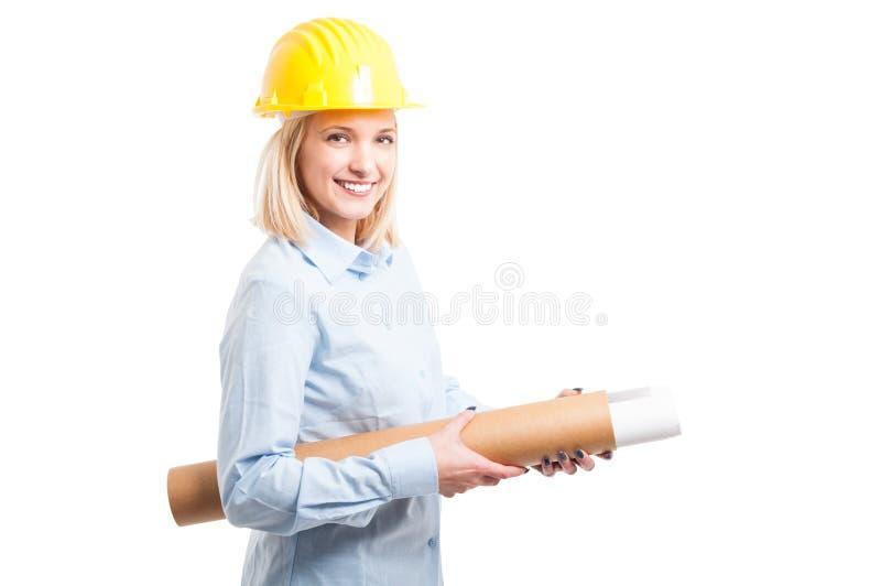 头戴黄色盔甲的妇女建筑师拿着图纸 免版税库存图片