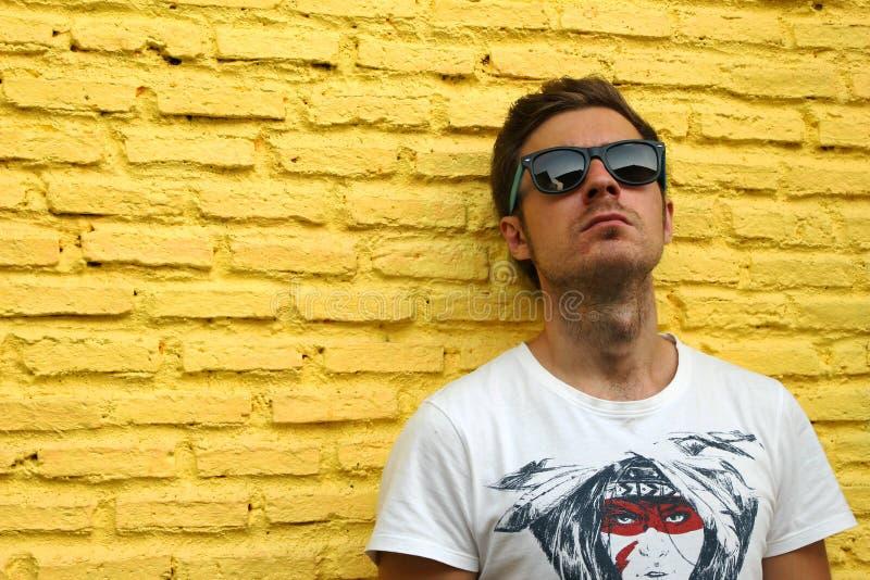 黄色砖墙背景的年轻人  免版税库存图片