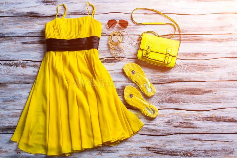 黄色礼服、太阳镜和袋子 免版税库存图片