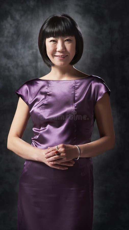 紫色礼服的亚裔妇女 免版税库存图片