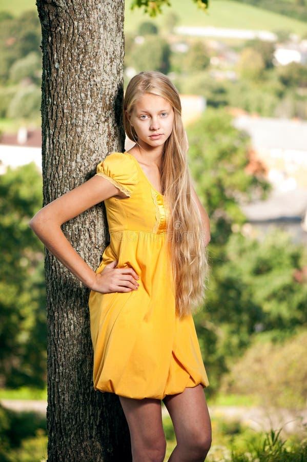 黄色礼服的女孩反对农村风景背景 库存图片