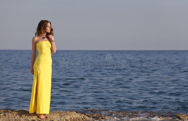 黄色礼服的妇女在海滩 库存图片