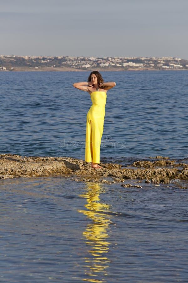 黄色礼服的妇女在海 免版税库存照片
