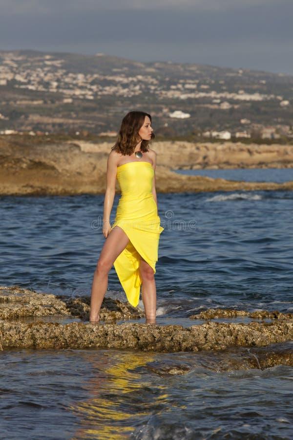黄色礼服的妇女在水中 图库摄影