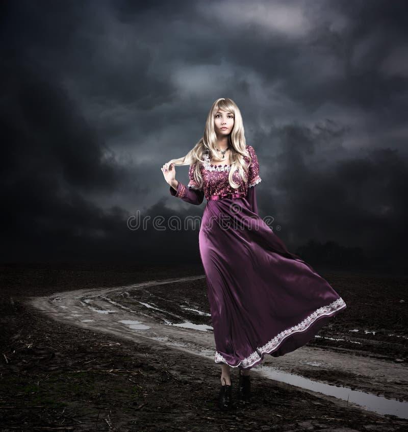 紫色礼服的妇女走在肮脏的路的 免版税库存照片