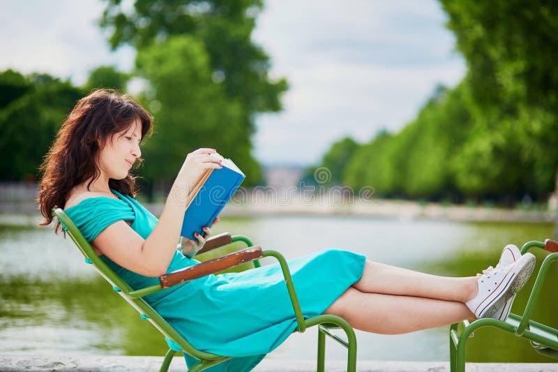 绿色礼服的妇女读一本书的在巴黎,法国Tuileries庭院里  库存照片