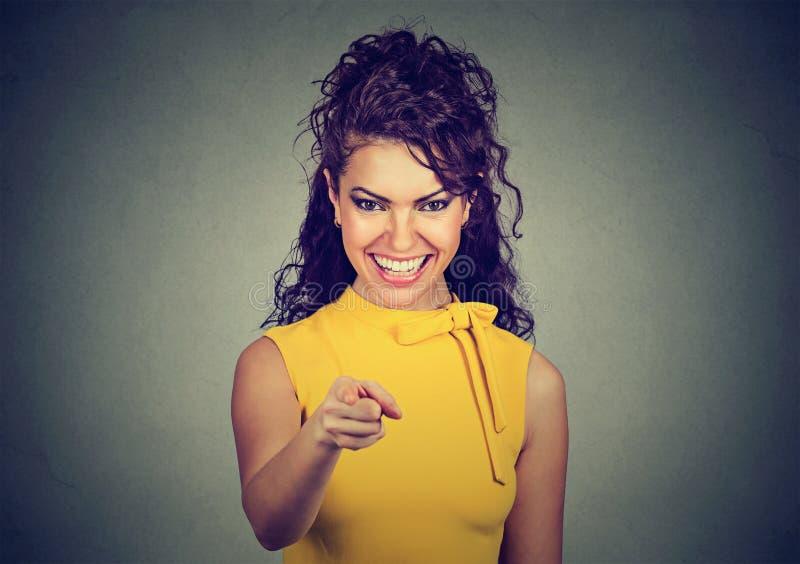 黄色礼服的微笑的女商人把手指指向的观察者 免版税库存图片