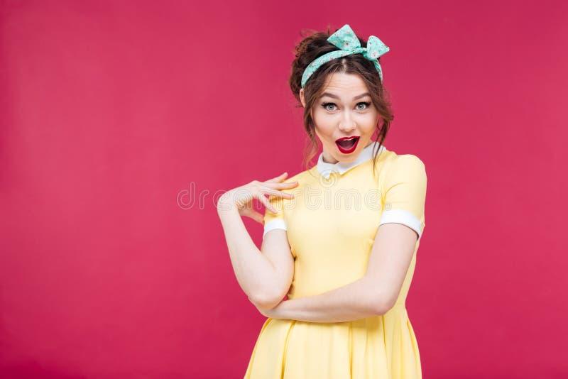 黄色礼服的惊奇愉快的画报女孩 库存图片