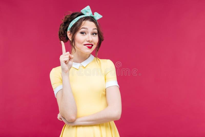 黄色礼服的指向可爱的微笑的画报的女孩  库存图片