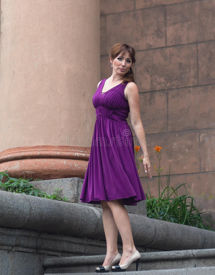 紫色礼服的美丽的妇女在专栏附近 图库摄影