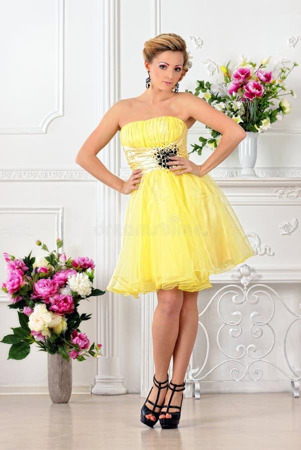 黄色礼服的美丽的妇女在豪华演播室。 免版税库存照片