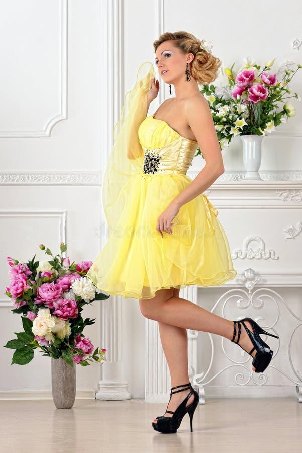 黄色礼服的美丽的妇女在豪华演播室。 库存图片