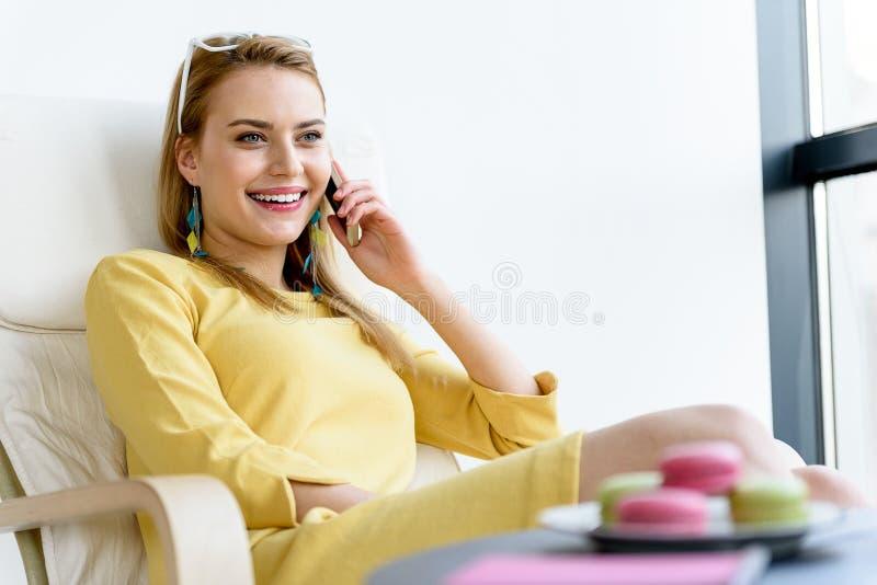 黄色礼服的迷人的夫人享受电话谈话的 免版税图库摄影