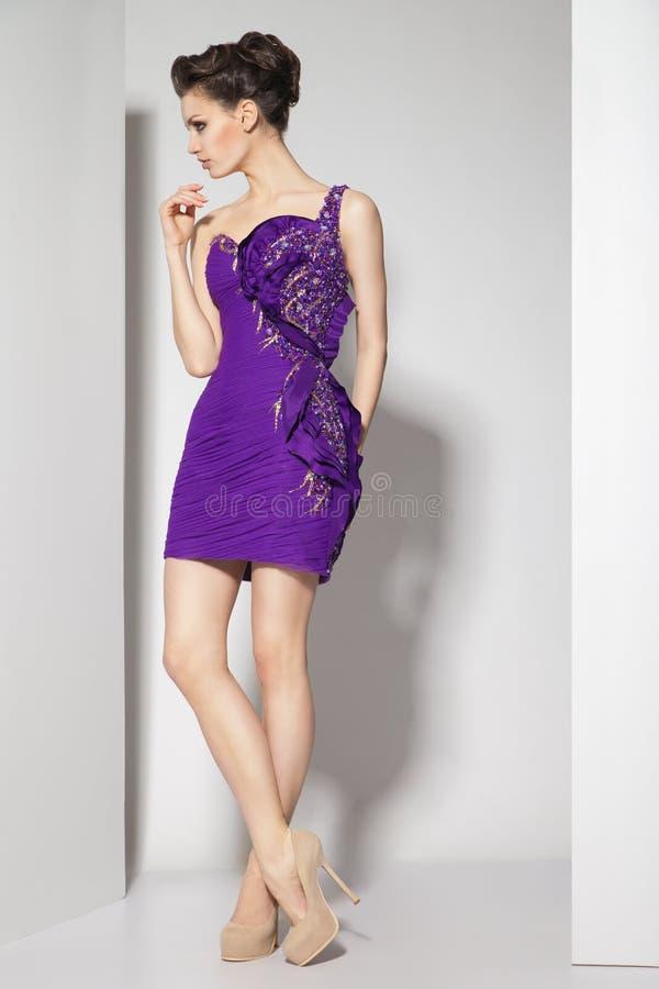 紫色礼服的年轻美丽的浅黑肤色的男人在白色 图库摄影