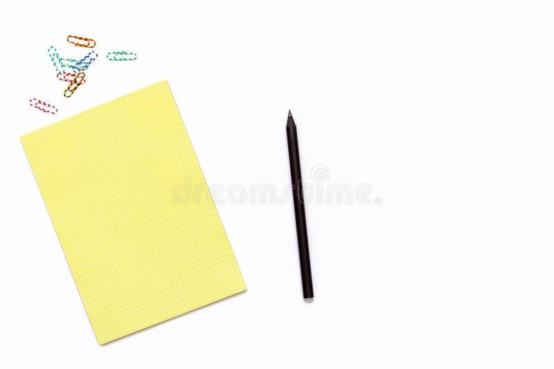 黄色笔记薄、铅笔和一个纸夹 工作地点的最小的企业概念在办公室 库存图片