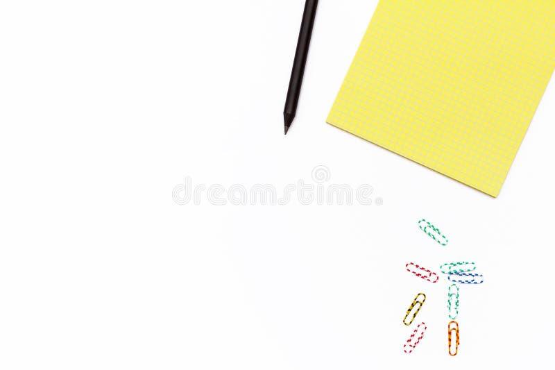 黄色笔记薄、黑铅笔和色纸夹子在白色背景 最小的企业概念 平的法律 免版税库存照片