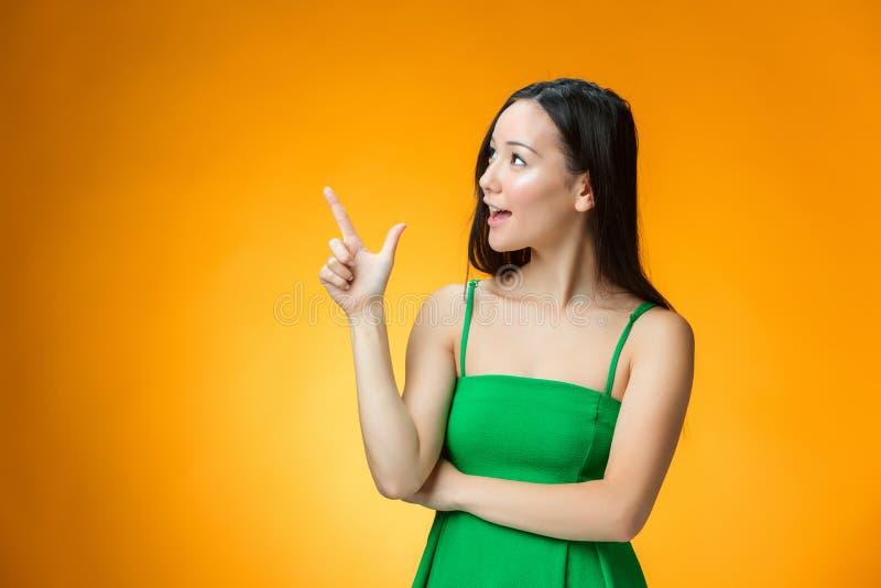 黄色背景的愉快的中国女孩 免版税图库摄影