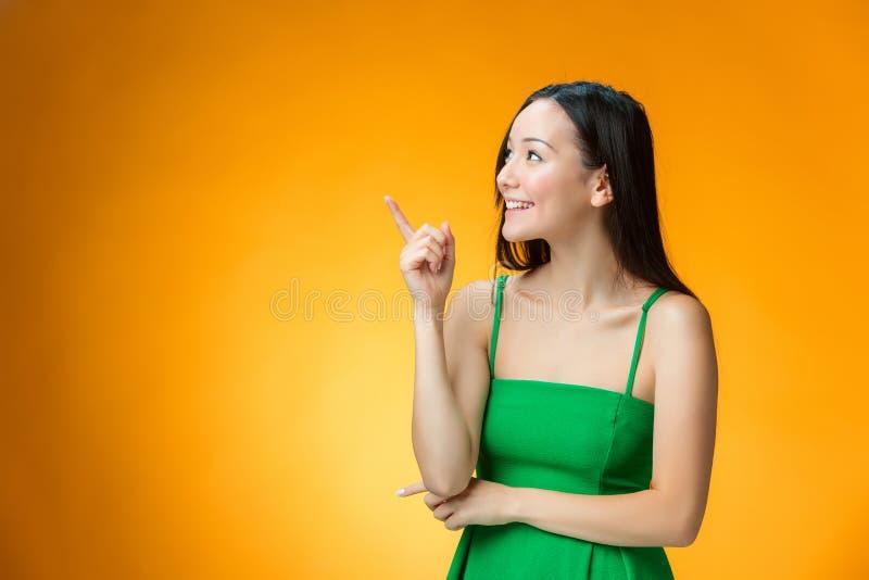 黄色背景的愉快的中国女孩 免版税库存照片