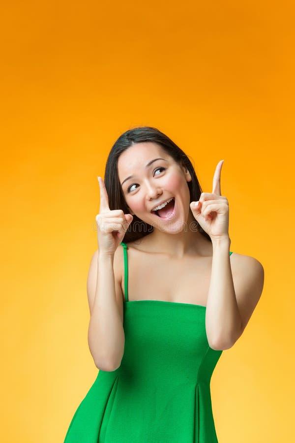 黄色背景的愉快的中国女孩 免版税库存图片