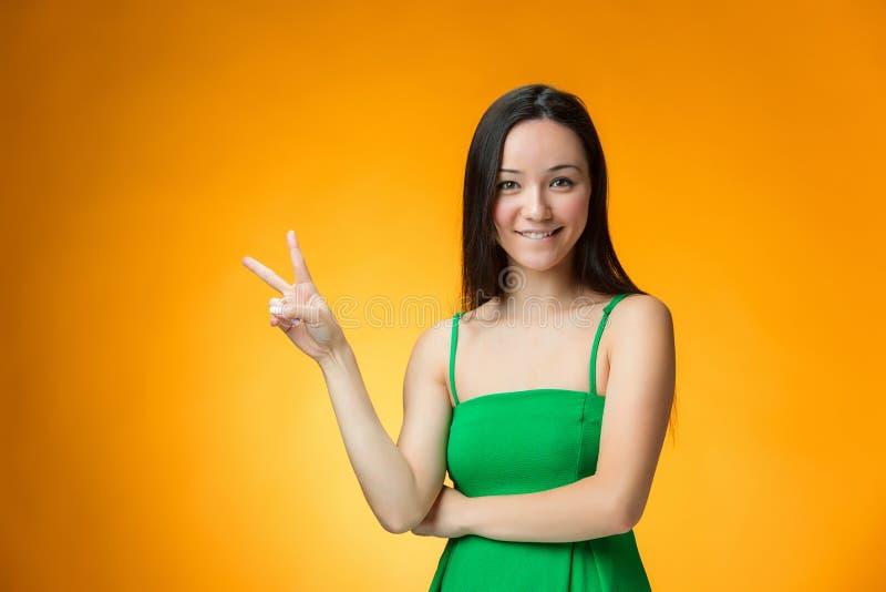 黄色背景的愉快的中国女孩 图库摄影