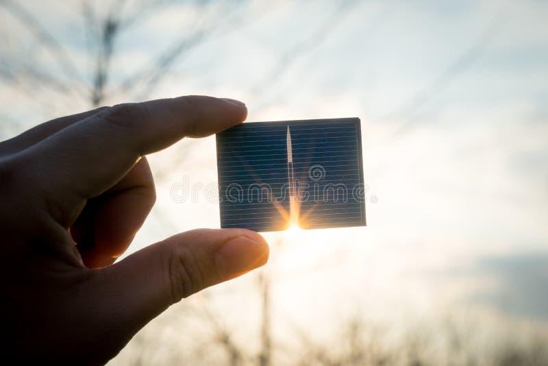 绿色能量,光致电压的太阳能电池用手 免版税库存图片