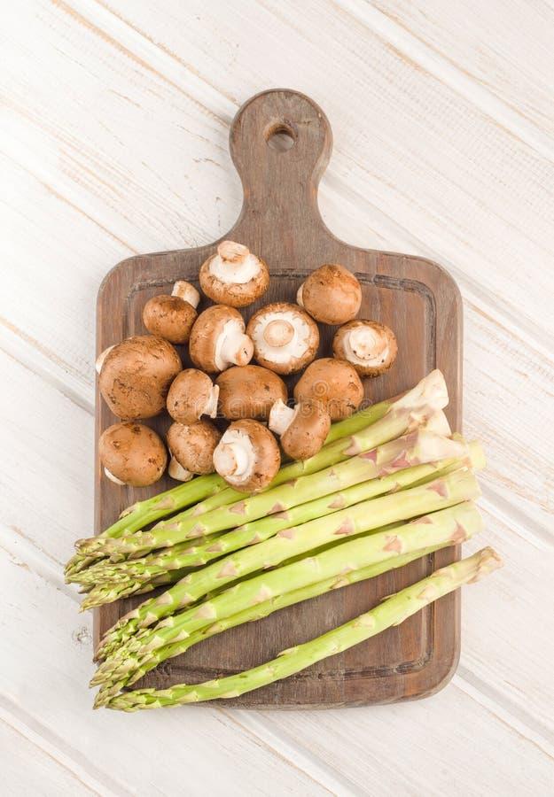 绿色芦笋和未加工的棕色蘑菇 库存图片