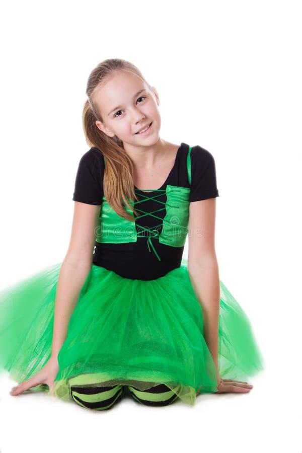 绿色芭蕾舞短裙的微笑的舞蹈家女孩避开坐 免版税库存图片